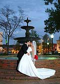 A bride and groom kissing in front of a fountain