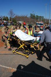 A DUI Reenactment showing a person being pushed on a stretcher by firefighters