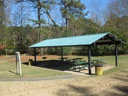 The Picnic Shelter at Merrit Park with tables under it and trees all around it