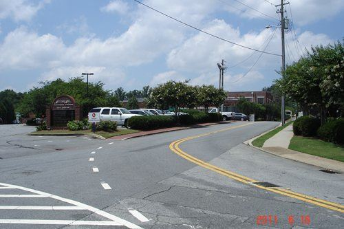 A curved two lane road with a parking lot on the left and trees and a sidewalk on the right