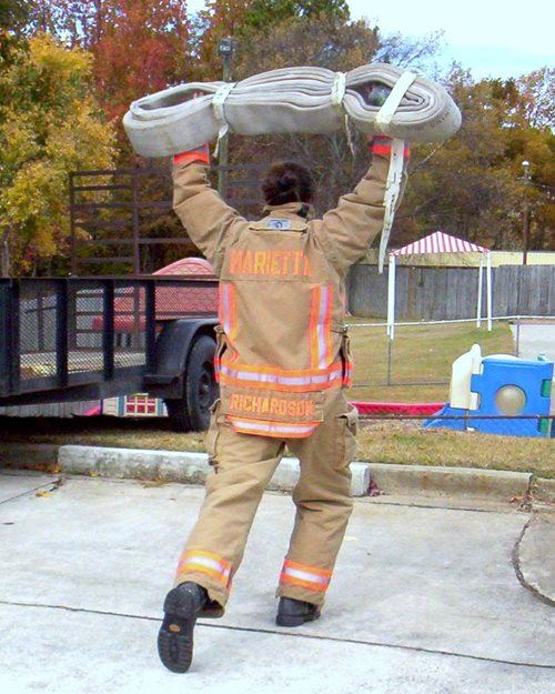 A firefighter doing highrise overhead lunges